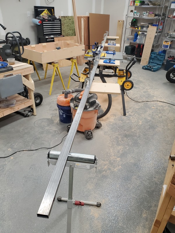 View of a contractor table saw with a 20 foot long fence, supported by roller stands
