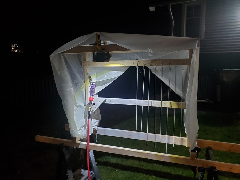 Night-time photograph of a rickety-looking structure covered in plastic, with an LED worklight